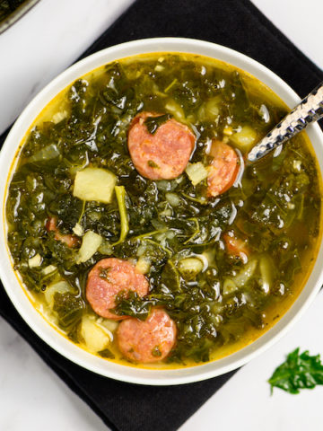 A bowl of LInguica Kale Soup in a white bowl.