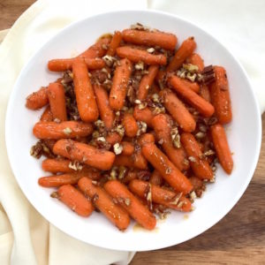 Glazed Spiced Baby Carrots with Pecans in serving bowl.