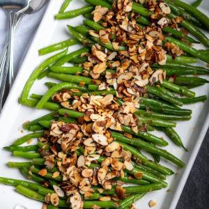 Green bean almandine on a white platter.