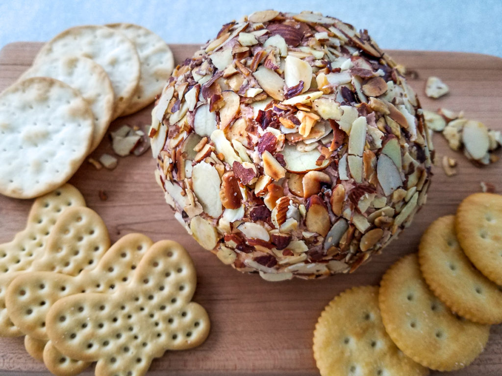 A port wine cheese ball coated in sliced almonds surrounded with crackers on a board.