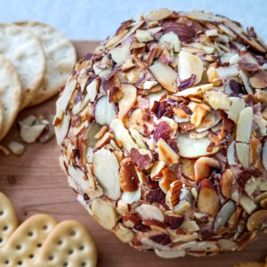 A port wine cheese ball coated in sliced almonds on a board.