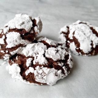Three baked chocolate crinkle cookies.