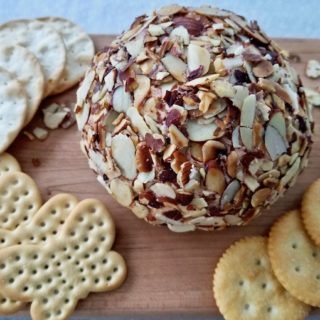 Port wine cheese ball on board with crackers.