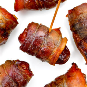 Bacon wrapped dates on a baking sheet.