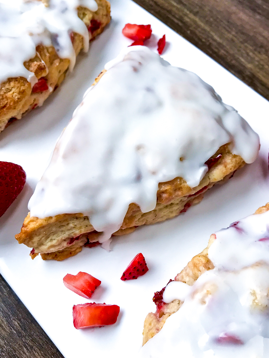 Three iced strawberry scones on a white platter.
