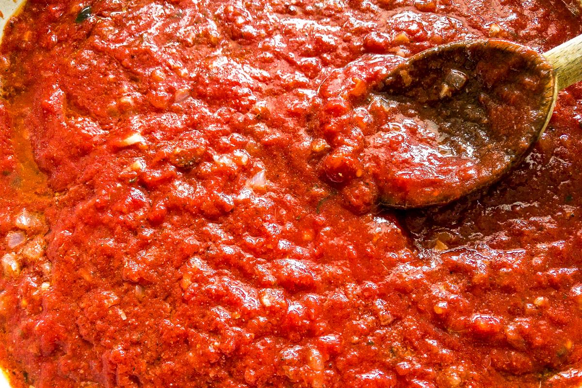 A wooden spoon stirring tomato sauce.