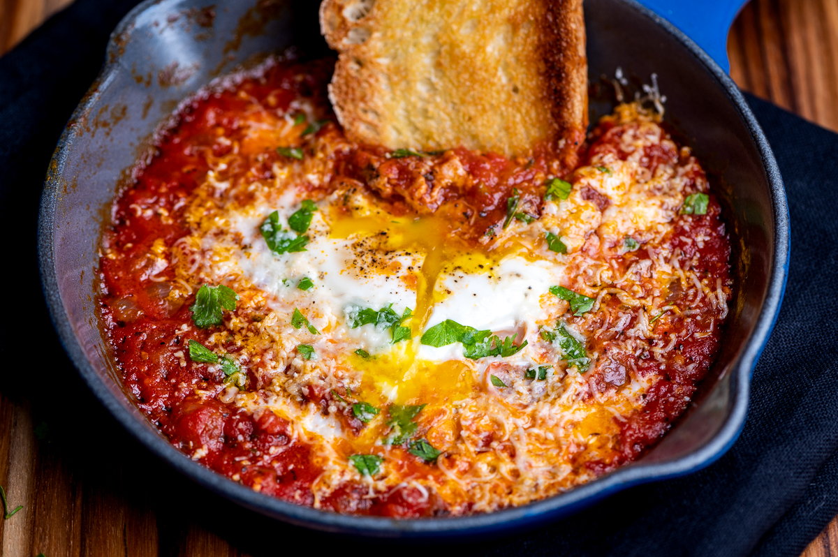 Eggs in purgatory in a small skillet with with a hunk of crusty bread dipping into the sauce.