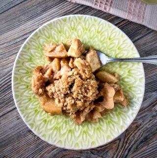 A scoop of apple crisp on a plate.