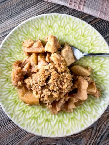 A scoop of apple crisp on a plate.