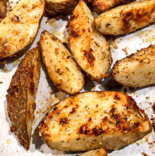 Baked potato wedges on a baking sheet.