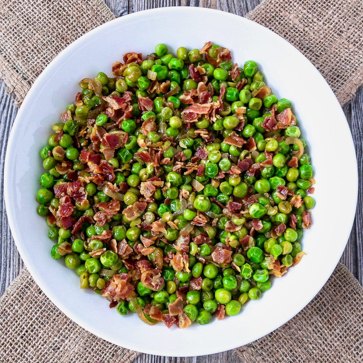 Peas and pancetta in a white bowl.