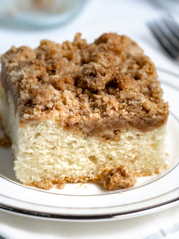 A slice of crumb coffee cake on a white plate.