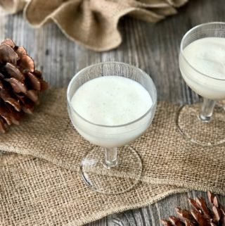 A glass of homemade Italian cream liqueur surrounded with pinecones.