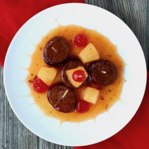 A plate of kielbasa, cherries, and pineapple.