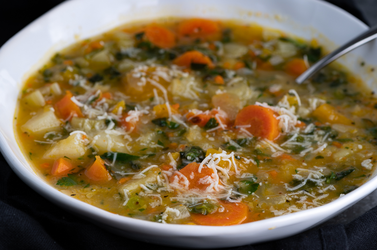 An angled view of sweet potato vegetable soup with grated cheese.