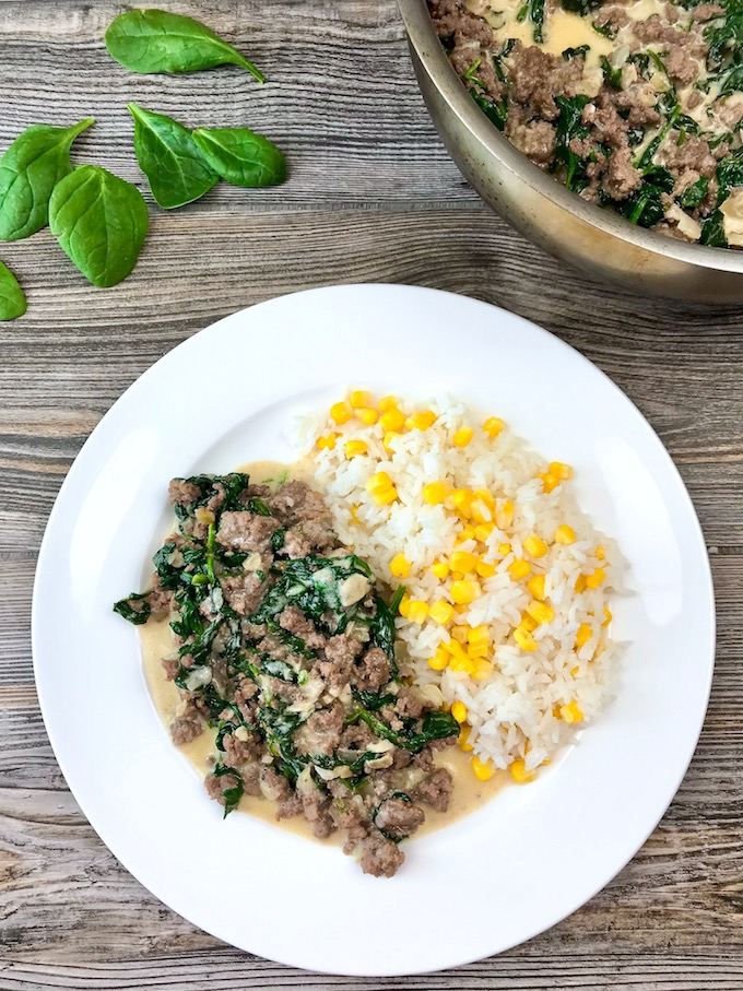 A white plate with a serving of ground beef with spinach and cream with a side of rice and corn.