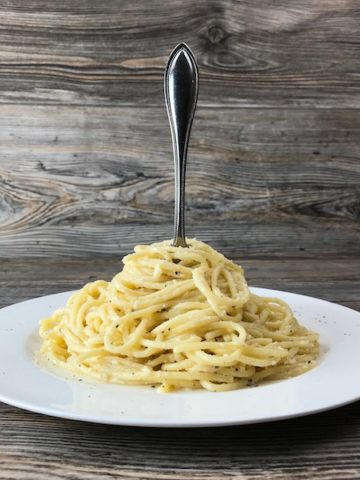 Spaghetti with Garlic Butter and Cheese on a plate with a fork standing up in the middle of it.
