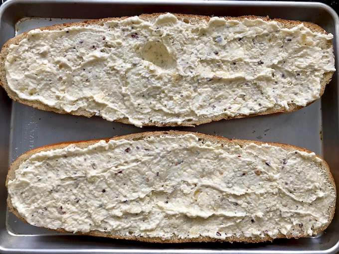Creamy garlic butter spread on a split Italian loaf ready to be broiled.