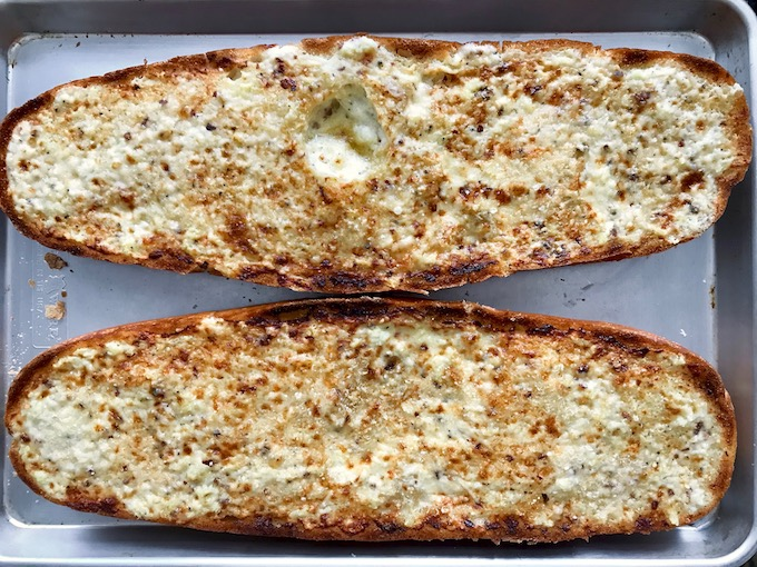 Creamy cheese bread broiled on a baking sheet.
