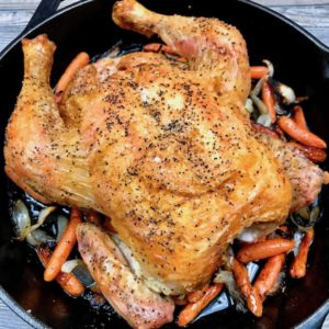 Simple Roast Chicken on top of caramelized onions and carrots in a skillet.