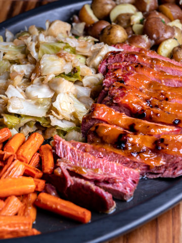 An angled view of a black tray with sliced corned beef, baby potatoes, sautéed cabbage, and roasted carrots.