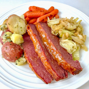 A plate of corned beef, cabbage, buttered potatoes, and roasted carrots.