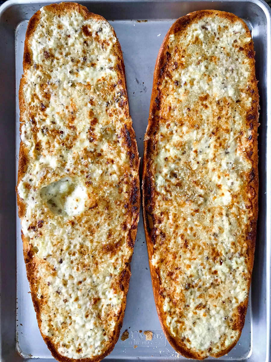 Creamy garlic bread just broiled on a baking sheet.