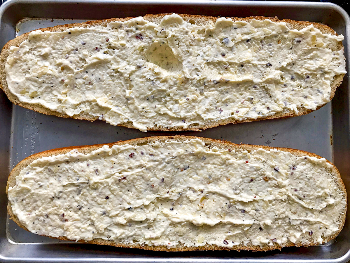 A split loaf of Italian bread topped with a cheesy garlic spread on a baking sheet.