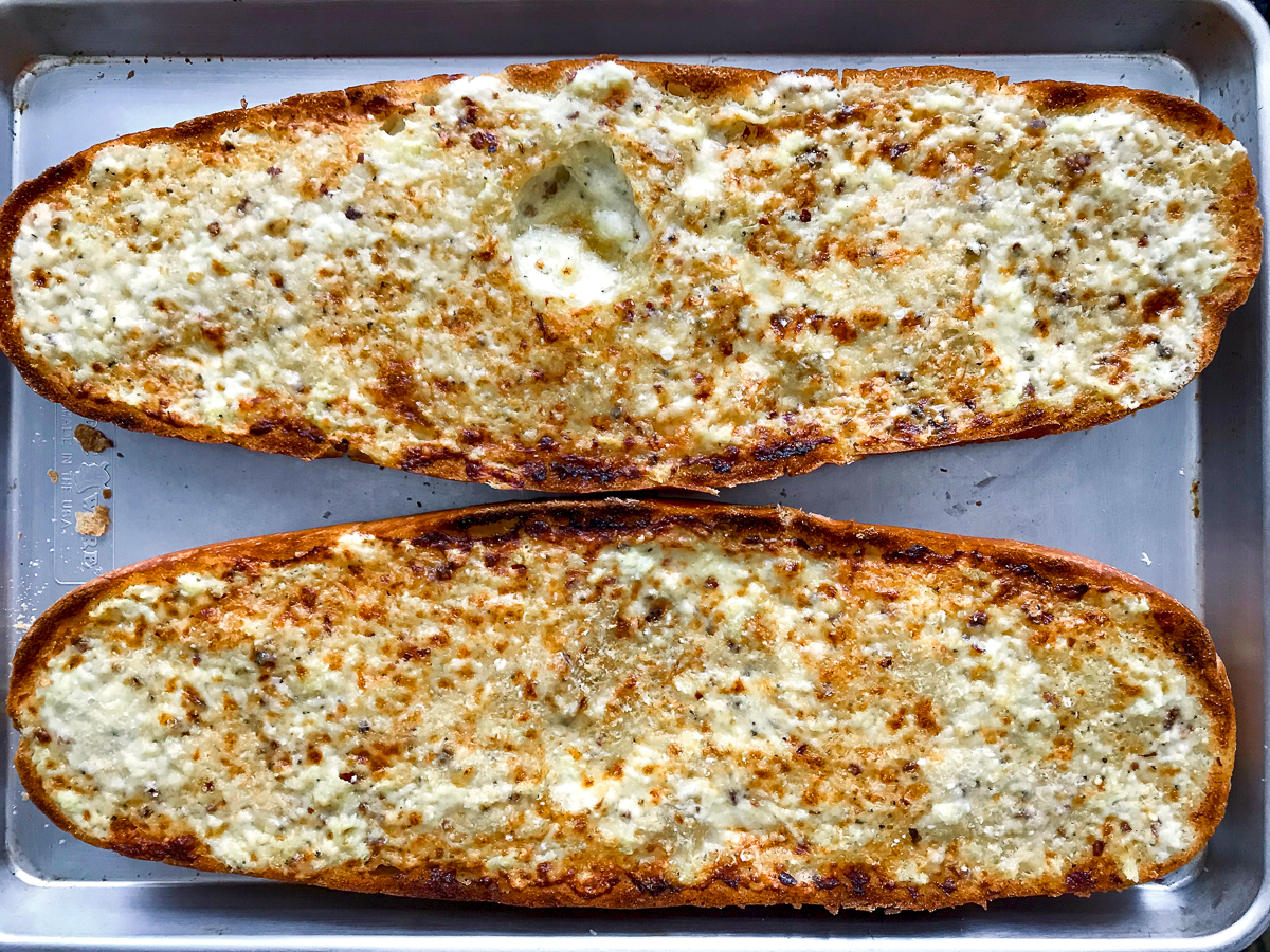 Two halves of browned garlic bread on a baking sheet.