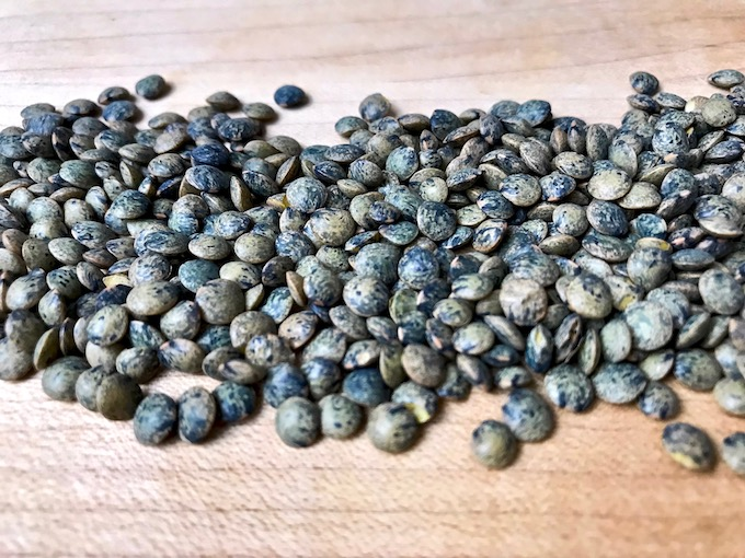 Le Puy lentils spread out on a board.