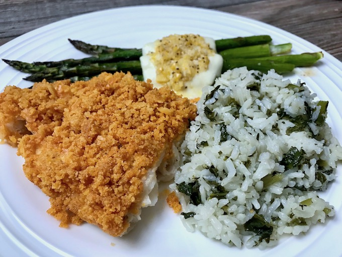 A serving of New England Baked Haddock on a plate with asparagus and kale rice.