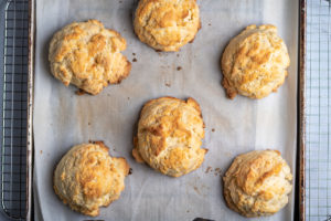 Six baked biscuits on a baking sheet.