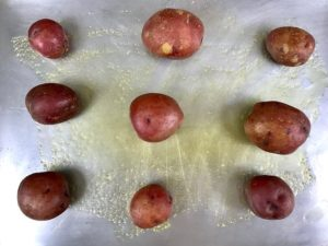 Nine red potatoes on oiled baking sheet.