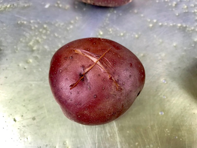 A small red potato with an X on top.