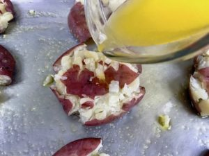 Pouring butter over smashed potato.