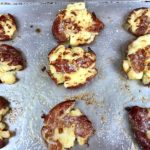 Golden smashed potatoes on a baking sheet.