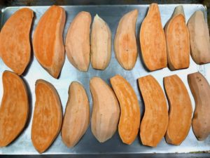Sliced sweet potatoes on a hot oiled baking sheet ready to go into the oven.