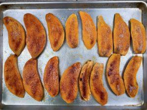 Roasted sweet potato planks on a baking sheet.