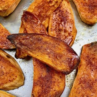 Roasted spiced sweet potato planks on a baking sheet.