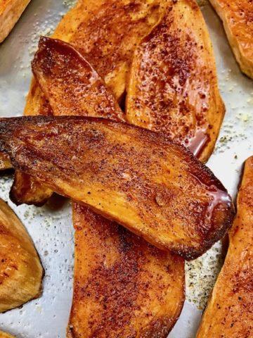 Roasted spiced sweet potato planks on a baking sheet.