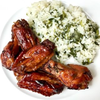A plate of teriyaki chicken wings and rice.