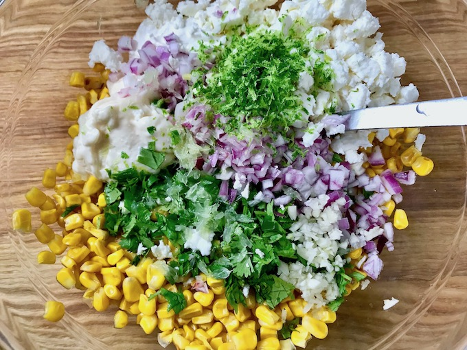 Ingredients for Mexican street corn salad in a bowl.