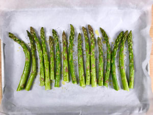 Asparagus coated with olive oil, salt, and pepper on a baking sheet.