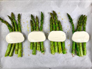 Placing fresh mozzarella onto roasted asparagus.