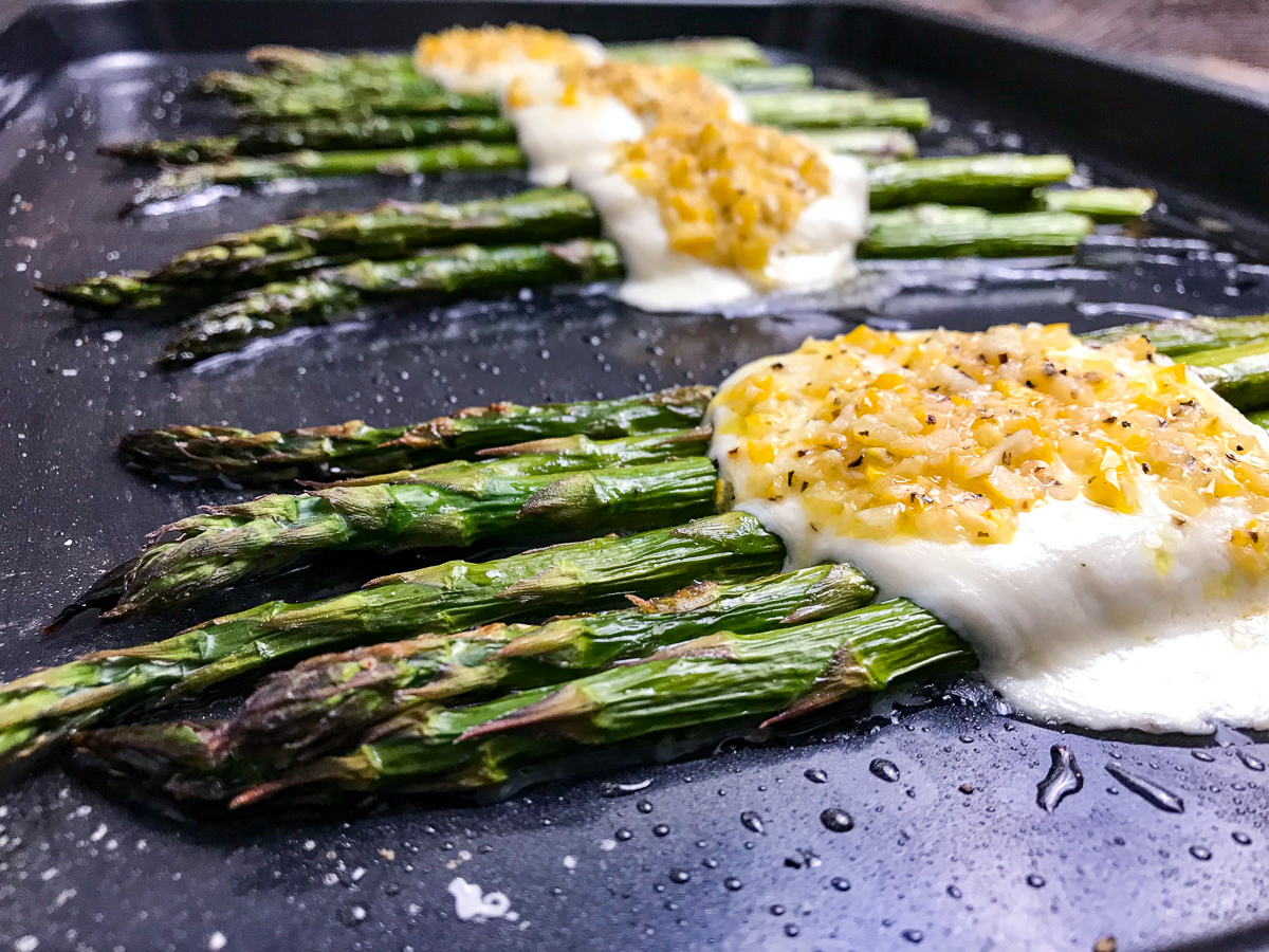Angled view of roasted asparagus with mozzarella on a black baking sheet.