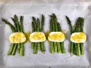 Roasted asparagus with melted mozzarella and lemon dressing on baking sheet.