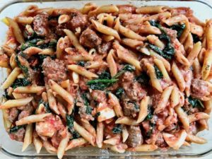 Sausage pasta bake with mozzarella in a baking dish.