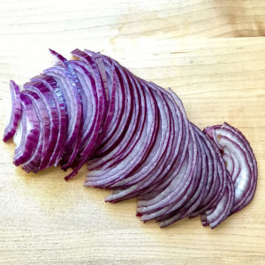 Thinly sliced red onions on a cutting board.