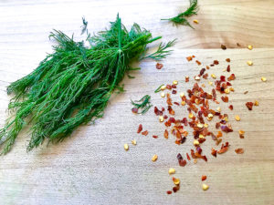 Fresh dill and crushed red pepper on a cutting board.