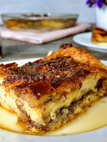 A slice of French toast casserole with maple syrup on a plate.
